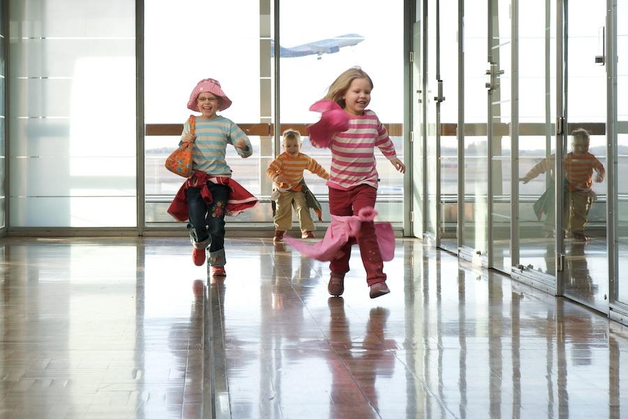 Lapset juoksevat lentokentällä
