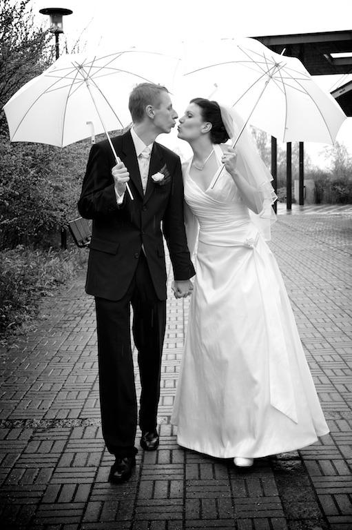 Suulan ja Teemun suudelma sateenvarjojen alla
