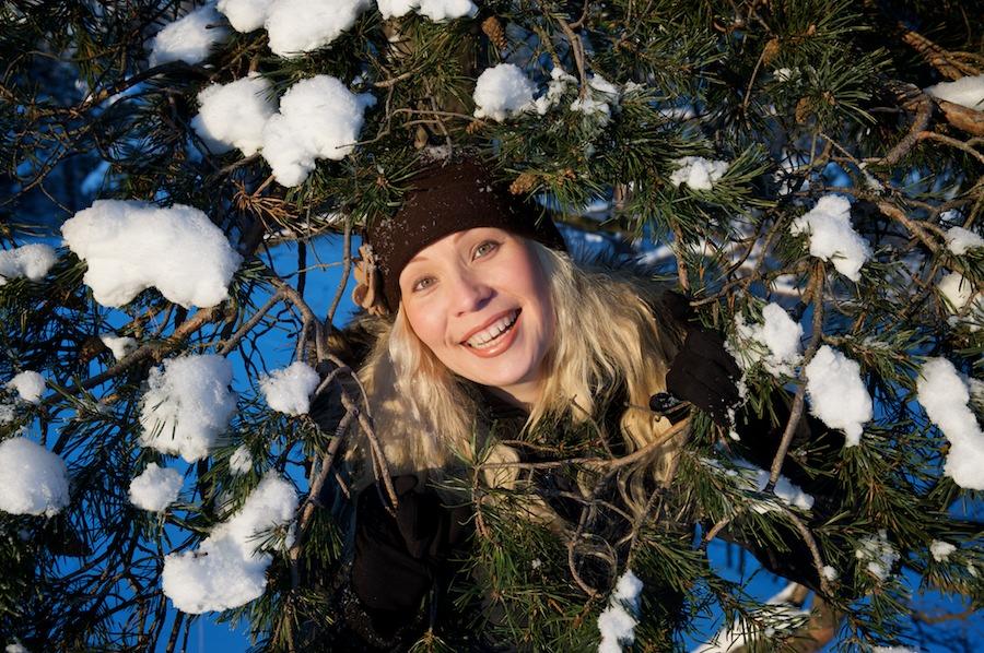 Heidi kurkistaa lumisen männyn oksien välistä